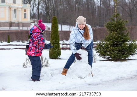 Mother with child making snowman with snow in winter park