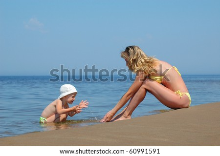 Mother with child plays on the beach
