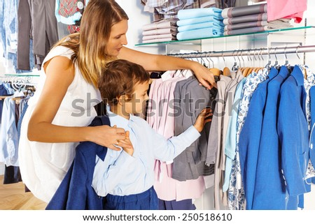 Mother with child searches clothes while  shopping - stock photo