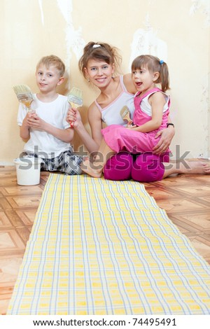 Mother with children doing repairs together, wallpaper on the floor - stock photo
