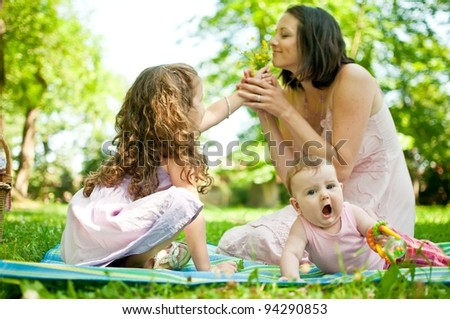 Mother with children having happy time - smelling flowers - stock photo