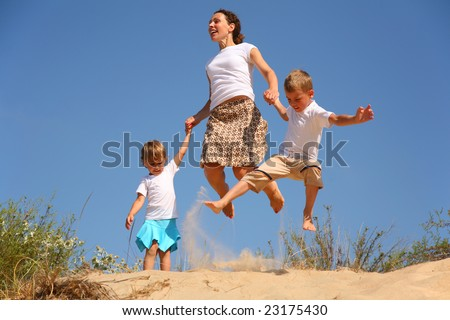 Mother with children jumping on sand