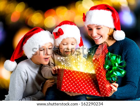 Mother with children opens the box with gifts on the christmas holiday - indoors - stock photo