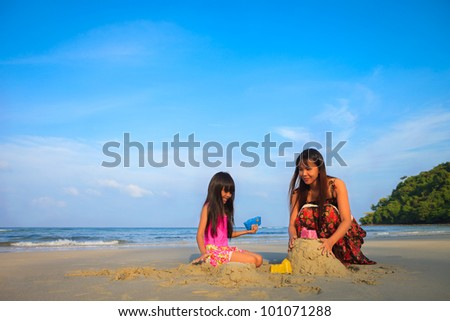 Mother with children playing with sand on beach with blue sky - stock photo
