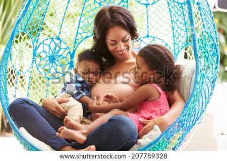 Mother With Children Relaxing On Outdoor Garden Swing Seat - stock photo
