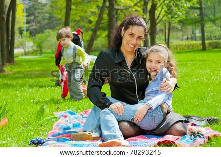 Mother with children resting and playing in the park