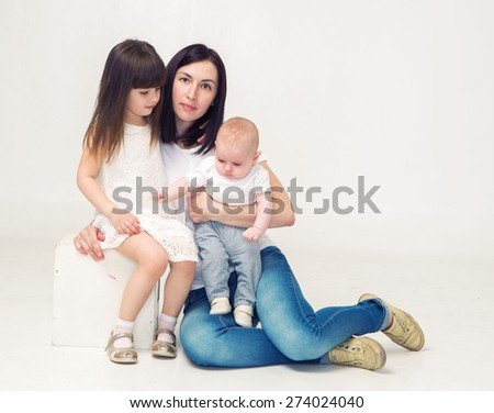 Mother with children's sister and brother portrait studio - stock photo