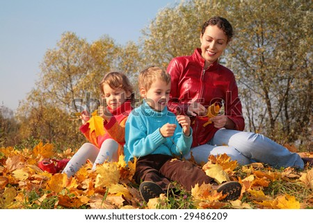Mother with children sit on fallen maple leaves
