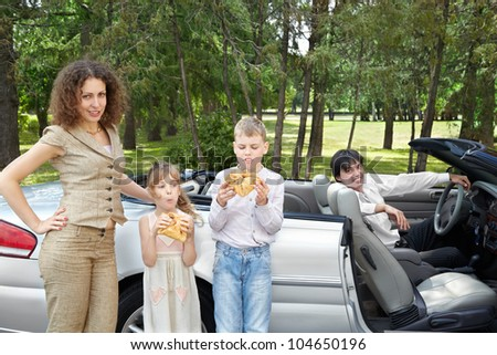 Mother with children stands near open top car, children eat samosa, father sits on driver seat.