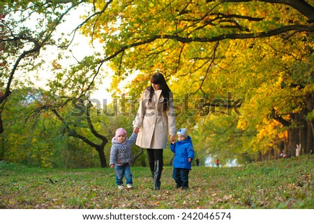 mother with children twins on a walk in the autumn park - stock photo
