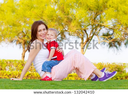 Mother with cute baby boy sitting down on green grass in spring park, mom with son enjoying springtime nature, happy family spending time outdoors - stock photo