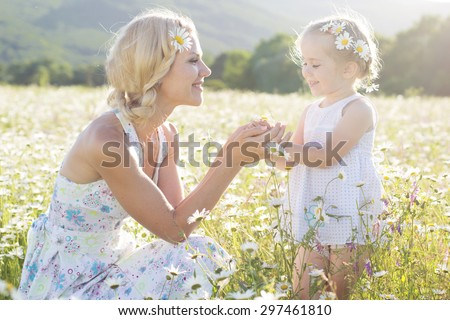 Mother with cute little daughter are wearing white dresses in the chamomile field, summer time - stock photo