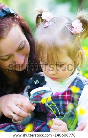 mother with daughter are playing on green meadow examining field flowers using magnifying glass - stock photo