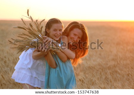 mother with daughter at the wheat field  - stock photo
