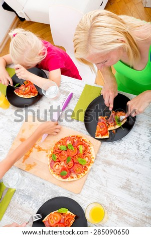 mother with  daughter eating Pizza for lunch or dinner.  - stock photo