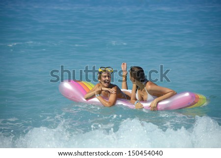 Mother with daughter getting fun at the inflatable mattress on the big wave - stock photo