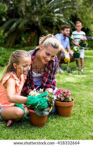 Mother with daughter holding flower pots against family at yard