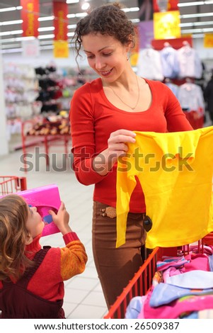 Mother with daughter in clothes shop - stock photo