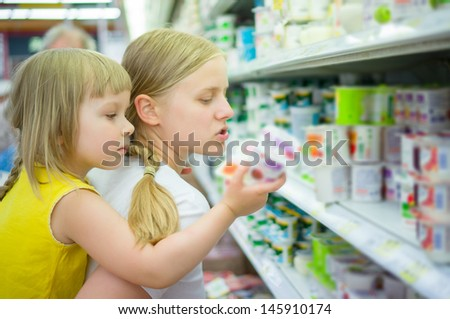 Mother with daughter on back select products in supermarket - stock photo