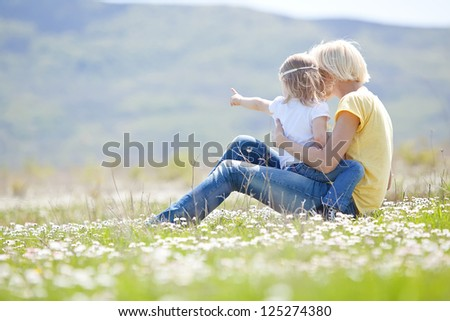 Mother with daughter on the  meadow