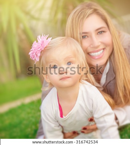 Mother with daughter playing outdoors, lying down on fresh green grass field in the park, happy family spending summer vacation - stock photo