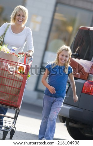 Mother with daughter pushing grocery cart full of groceries - stock photo
