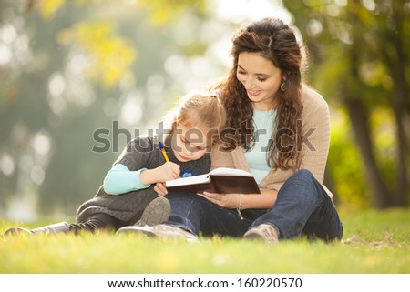 Mother with daughter read a book in the park - stock photo