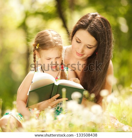 Mother with daughter read a book in the park. Happy family concept. Beauty nature scene with family outdoor lifestyle. Happy family resting together on the grass. Happiness and harmony in family life.