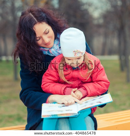 Mother with daughter read a book in the park. Happy young mother with her daughter at park - stock photo