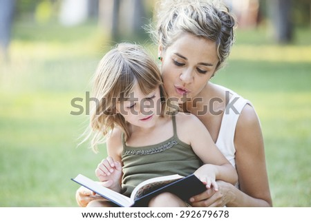 Mother with daughter reading a book in the park - stock photo