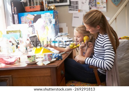 Mother With Daughter Running Small Business From Home Office