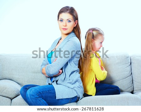 Mother with daughter seat on sofa back to back. Woman with girl portrait. - stock photo