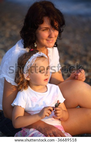Mother with daughter sits on seacoast