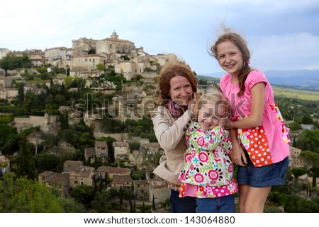 mother with daughters against the background of worldwide famous french provencale commune Gordes  - stock photo