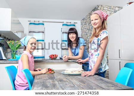 Mother with daughters baking a pie at home - stock photo