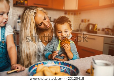 Mother with family haveing fun in kitchen - stock photo