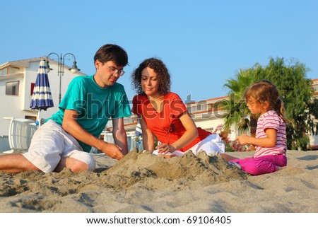 Mother with father and girl sit in  day-time on  beach and build hills from sand - stock photo