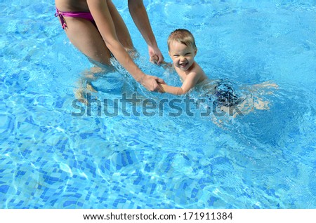 mother with happy baby in the swimming pool