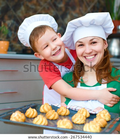 Mother with happy boy making bread in the kitchen - stock photo