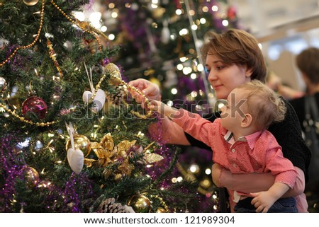Mother with her baby are near Christmas tree at home - stock photo