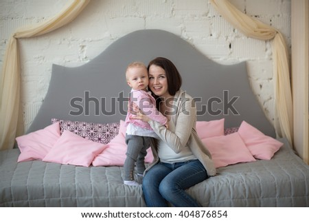 mother with her baby daughter playing on the couch in a real room, casual lifestyle, happy family. on the sofa - stock photo