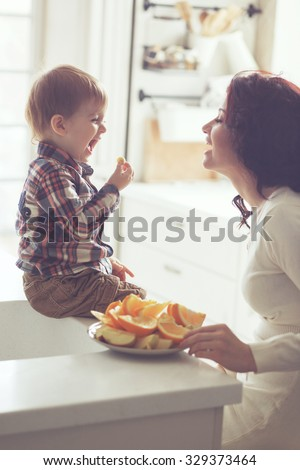 Mother with her baby eating fruits in the bright kitchen at home. Photo toned, still life. - stock photo