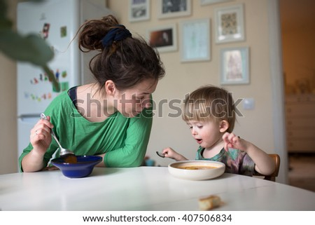 Mother with her baby eating soup in the bright kitchen at home,  real interior, Mom with dreadlocks, casual - stock photo