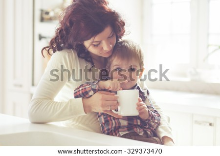 Mother with her baby having breakfast in the bright kitchen at home. Photo toned, still life. - stock photo