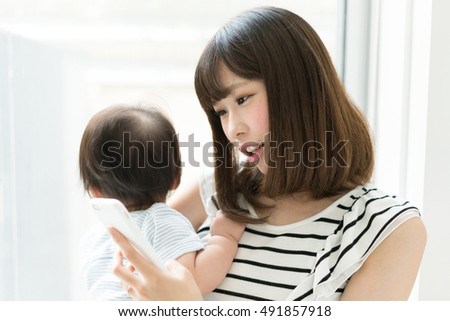 mother with her baby holding smart phone