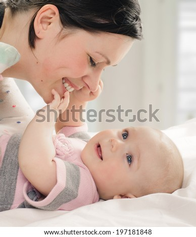 mother with her baby in the room with window background - stock photo