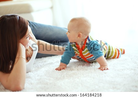 Mother with her baby playing on a carpet at home - stock photo