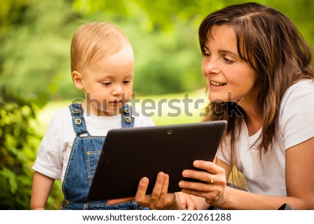 Mother with her baby watching together in tablet computer outdoor - stock photo