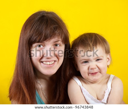 mother with her child  over yellow background