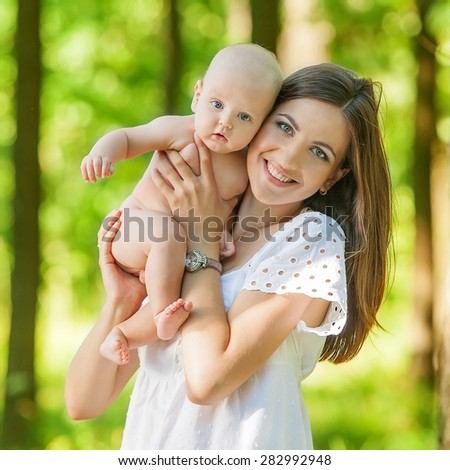 Mother with her child take rest in park - stock photo